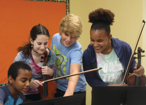 Instructor with young artists teaching classical music lessons at Florida Youth Orchestra